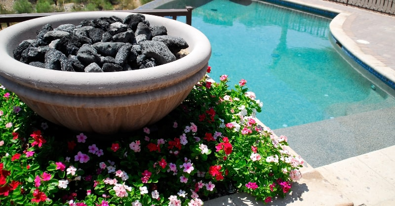 Fire bowl and colorful flowers near an inground swimming pool