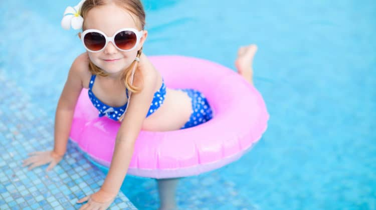 Little girl in swim ring posing in a swimming pool
