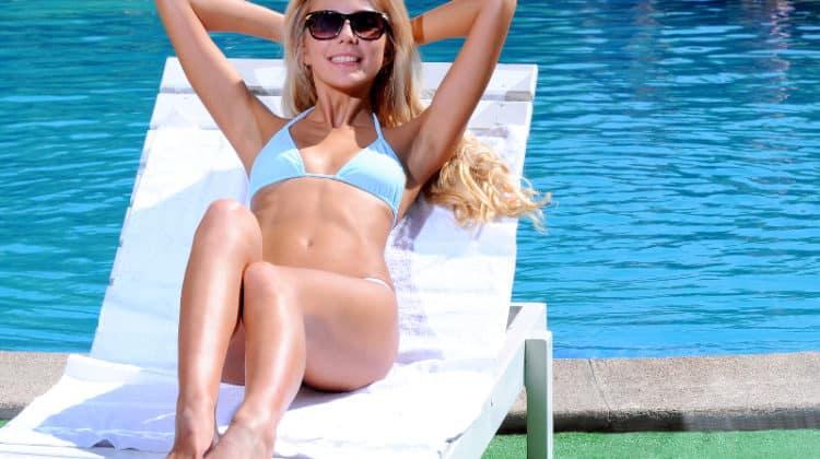 Woman sunbathing by a swimming pool