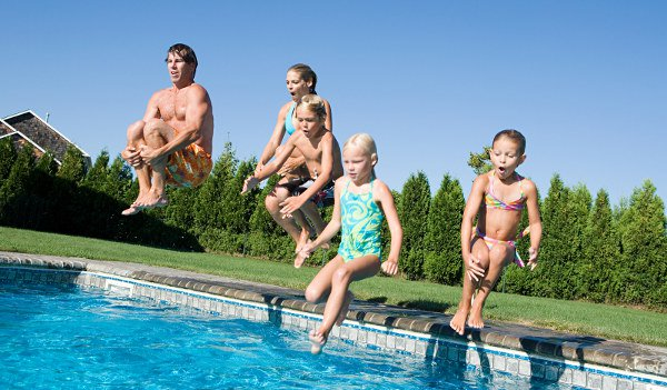 Five family members jumping into pool