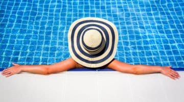 Woman relaxing in an inground swimming pool