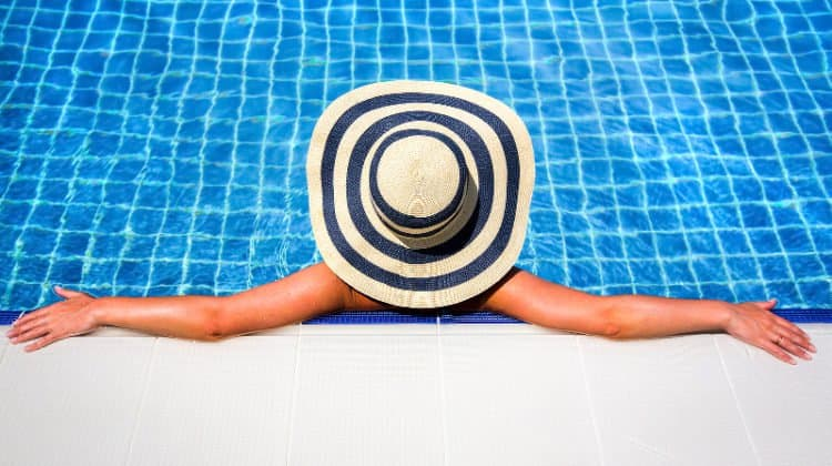Woman relaxing in an inground swimming pool