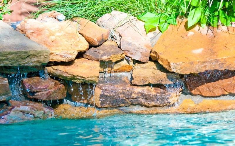 Rock waterfall pouring into an inground swimming pool