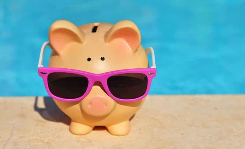 Piggy bank sitting on the deck of an inground swimming pool