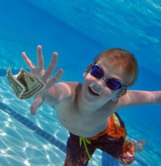 Boy reaching for dollar bill underwater