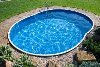 Small oval shaped backyard swimming pool