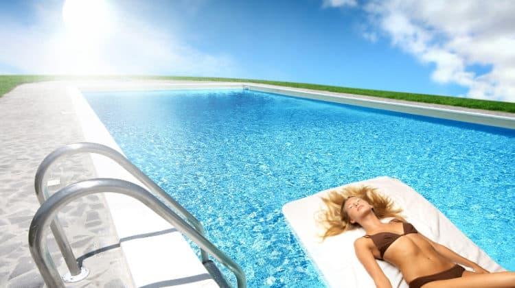 Lady in bikini floating on pool with bright sun overhead