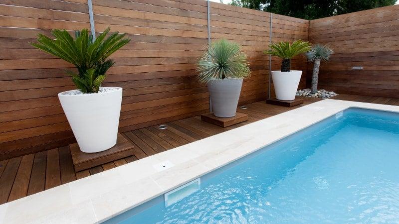 Wooden pool fence surrounding an inground swimming pool