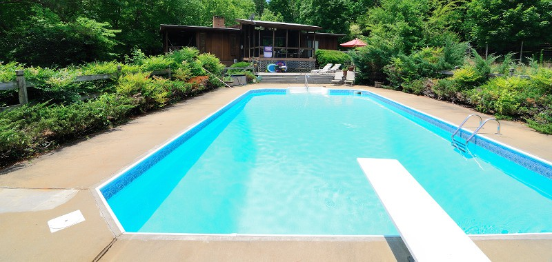 Rectangular pool with a diving board in the foreground