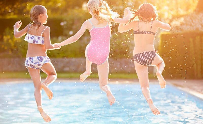 Three girls holding hands as they jump into a residential swimming pool