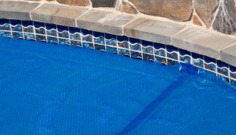 Closeup of the edge of an inground swimming pool covered with a blue bubble wrap solar pool cover