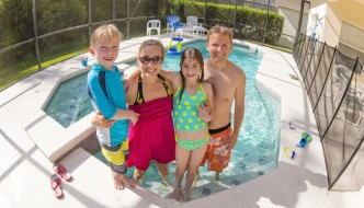Family of four posing in the shallow water of an enclosed inground swimming pool