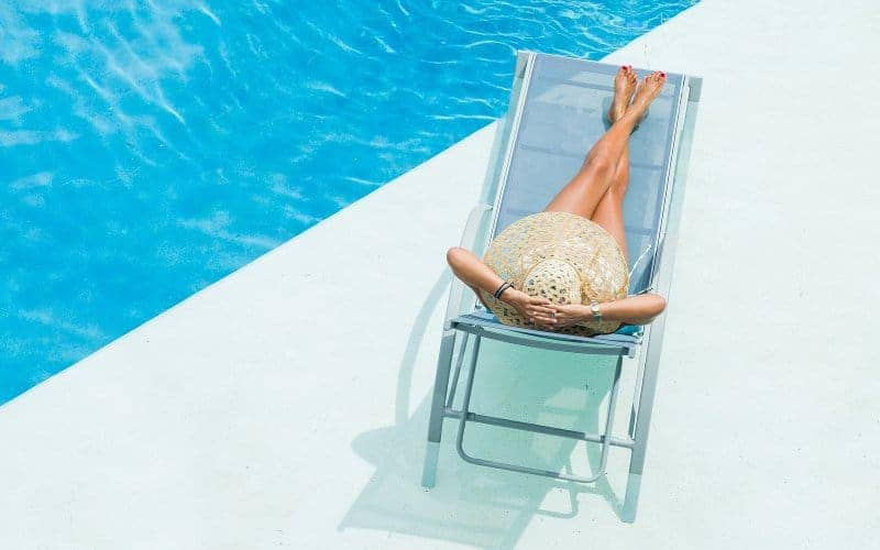 Woman relaxing on the deck of a luxury swimming pool