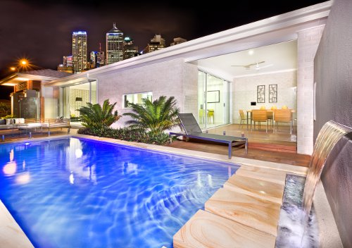 Beautiful modern backyard swimming pool with cityscape in the background