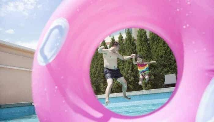 Father and young daughter jumping into an inground swimming pool, as seen through a pink inflatable tube