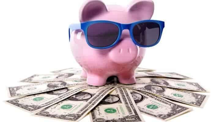 Piggy bank with sunglasses sitting on one dollar bills