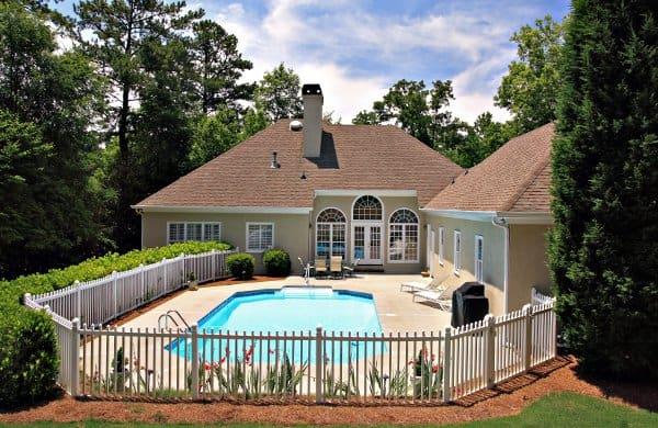 Picket fence surrounding a yard with an inground swimming pool