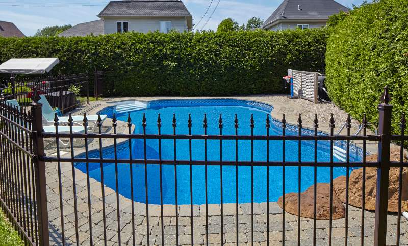 Closeup of a wrought iron fence with swimming pool in the background
