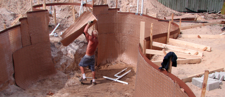 Picture of a man working on setting up the frame for an inground swimming pool