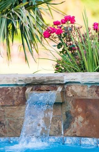 Stone waterfall on an inground swimming pool