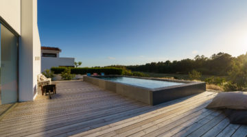 A semi inground swimming pool with wooden deck