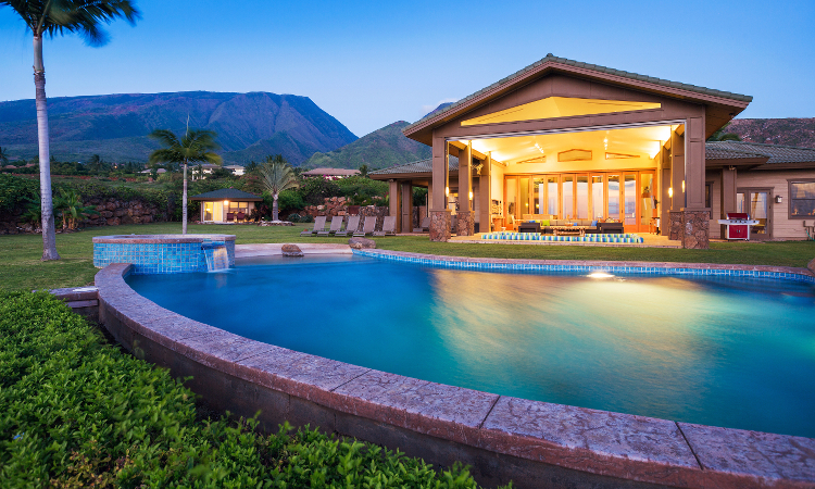 An upscale semi inground pool outside of a luxury home